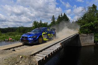 Higgins blasts across a bridge on New England Forest Rally's second day, pushing hard to maintain his overall event lead.