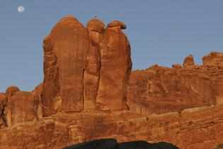 Climbers Conrad Anker, Max Lowe, and Rachel Pohl reach the top of the Three Penguins in Arches National Park, Utah.Courtesy of MacGillivray Freeman Films. Photographer: Barbara MacGillivrayVisitTheUSA.com