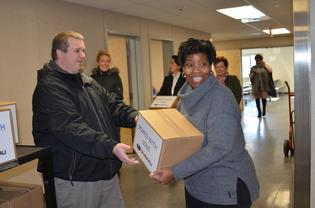 A Subaru employee hand delivers a box of classroom essentials to a Cream elementary school teacher
