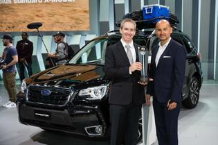 """Alan Bethke, senior vice president of Marketing, Subaru of America Inc. accepts the """"Top Mainstream Brand"""" Residual Value Award from Jim Nguyen, president of ALG at the Los Angeles Auto Show."""