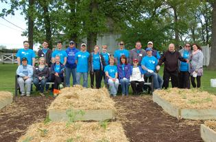 Subaru Volunteers along with some staff and participants from Lambs Farm gather for a final photo, showing off the finished garden.