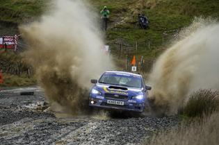 Higgin's 2015 WRX STI plows through a puddle at Wales Rally GB. Constant rain and winds made for a challenging three day rally.