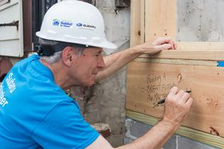 Tom Doll, President and COO for Subaru of America, writes a message of inspiration during a Camden Habitat for Humanity home construction on June 16, 2017.