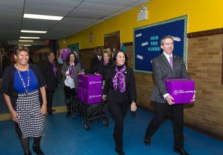 Subaru of America executives deliver book donation to Harry C. Sharp Elementary School students.