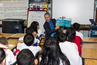 Subaru of America President & CEO Tom Doll reads to Harry C. Sharp Elementary School students, following Subaru book donation.