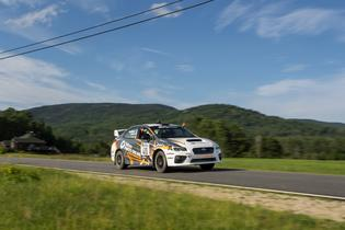 Lasek and Gelsomino wave in excitement on their transit to the podium at New England Forest Rally