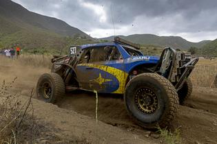 The Crosstrek Desert Racer gets its new blue and gold livery dirty on a deeply rutted section of the Baja course.