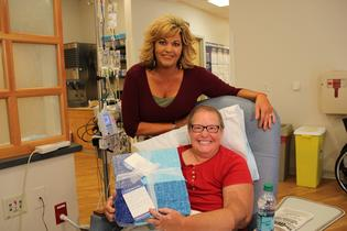 Wendy Schiavone, Sales Manager at Gateway Subaru, donates the first blanket to patient Brenda Rathel of Hebron, MD.